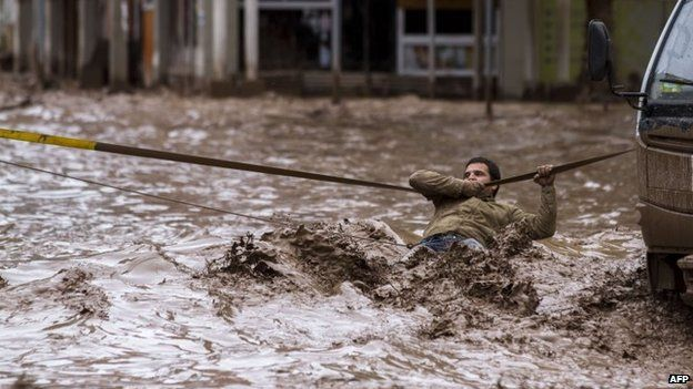 A man clings to a security line to cross a street flooded by the overflowing of the Copiapo River