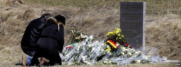 Relatives lay flowers in front of the monument in homage to the victims of Germanwings Flight 4U 9525 in Le Vernet, southeastern France, 27 March 2015.