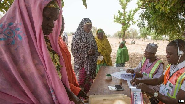Voters prepare to cast their ballots at a polling station set up under a tree on the outskirt of Kano during the presidential elections, 28 March 2015