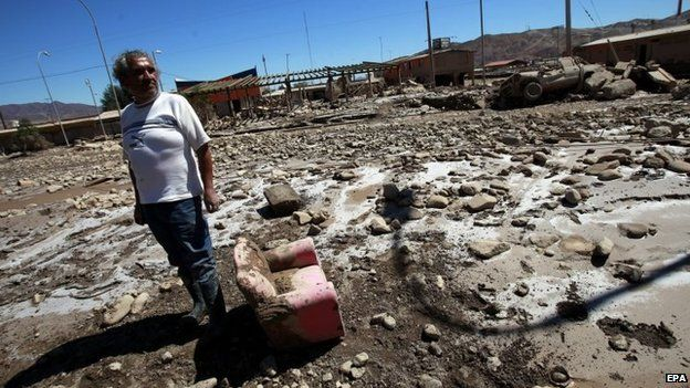 A man surveys the damage after torrential rains and floods in Diego de Almagro on 28 March 2015.
