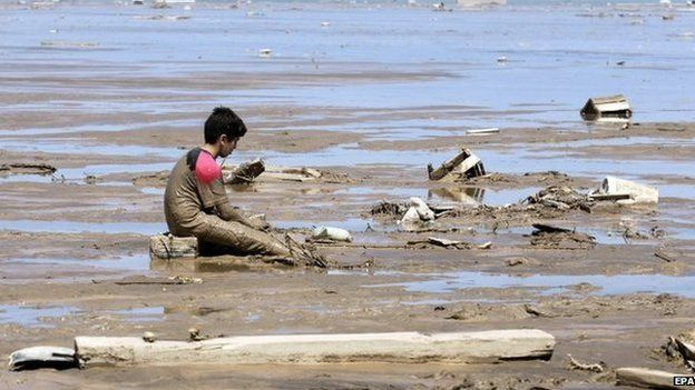 A child sits by wreckage after torrential floods and rains in Chanaral on 27 March 2015