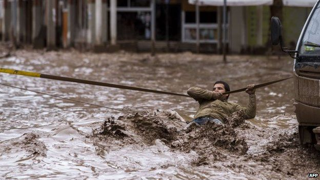 A man clings to a security line to cross a street flooded by the overflowing of the Copiapo River due to heavy rainfall that affected some areas of Copiapo on 26 March, 2015.