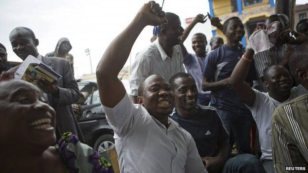 Supporters of presidential candidate Muhammadu Buhari cheer as they watch news coverage of election results favourable to them on a street in Lagos, 31 March 2015