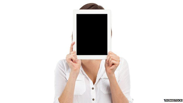 A woman holding a tablet in front of her face
