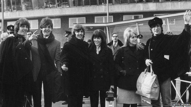 3th March 1965: British pop band The Beatles bidding farewell to their fans at London Airport as they leave to continue production of their film 'Help' in Austria. (Left to right) George Harrison (1943 - 2001), Paul McCartney, Ringo Starr (with Maureen) and John Lennon (1940 - 1980, with Cynthia)