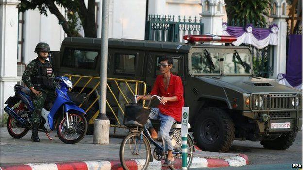 Man rides past soldiers in Bangkok, Thailand (2 April 2015)