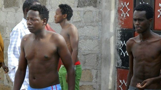 Some students without their shirts get out of a house where they seek refuge after escaping from an attack by gunmen in Garissa, Kenya, 2 April 2015