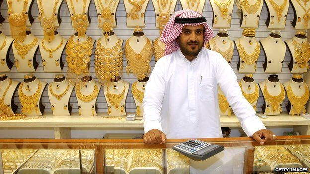 Shop keeper in front of a display of gold