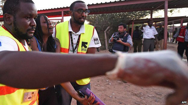 Paramedics lead away injured student at Garissa