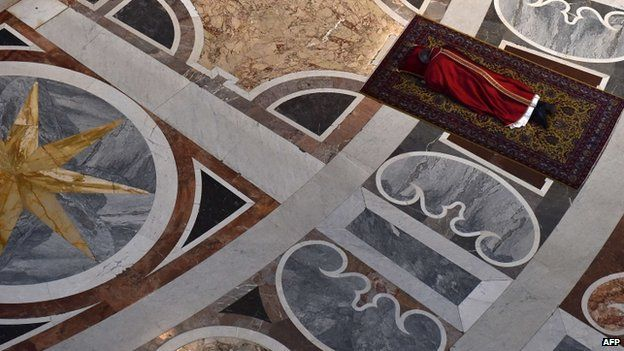 Pope Francis prays face down, on the floor of St. Peter's Basilica during the Celebration of Lord's Passion on Good Friday on April 3, 2015 in Vatican