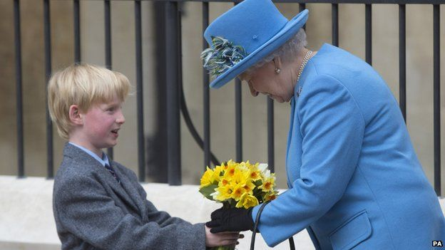 The Queen is presented with flowers by a boy