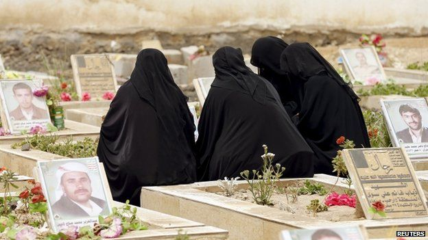 Women sit by the grave of a relative at a cemetery dedicated for Houthis killed in Yemen's ongoing conflict, in Sanaa 5 April 2015