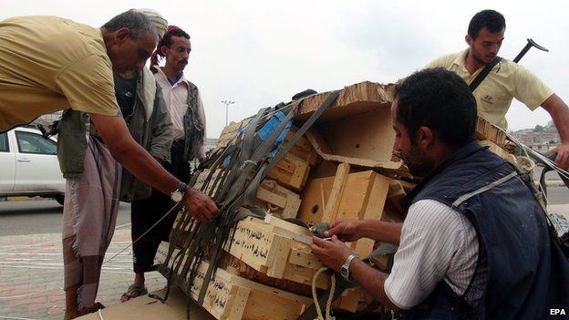 Tribal militiamen loyal to Yemeni President Hadi collect boxes full of weapons allegedly dropped by the Saudi-led coalition on 3 April 2015