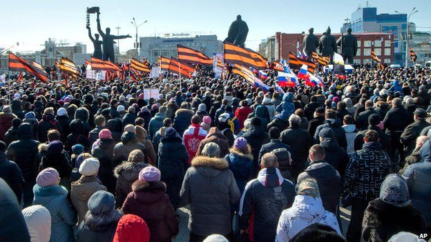 Several thousand people carry patriotic flags as they demonstrate against the proposed production of Wagner's Tannhauser, outside the state theatre in Novosibirsk (29 March 2015)