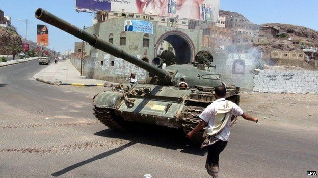 A man stands beside a tank manned by pro-government militia in Aden