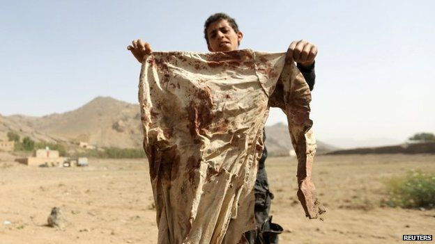 A boy holds a blood-stained garment at the site of an air strike in the Yemeni village of Bait Rejal