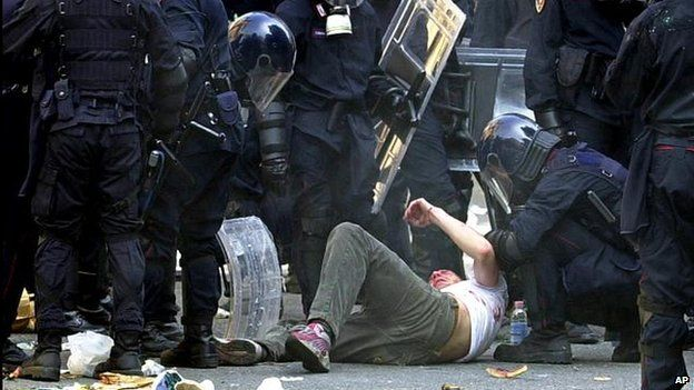 A demonstrator is subdued by riot police during clashes between protesters and police in downtown Genoa, Italy in July 2001