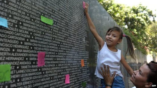 A girl places a note at the War Victims Memorial, during a ceremony to conmemorate the day of the disappeared children in San Salvador, El Salvador on March 29, 2012