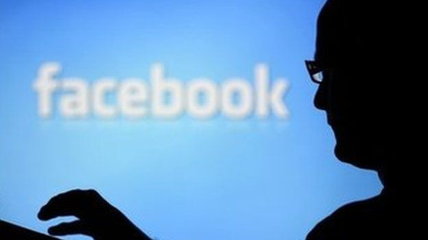 A man with a laptop is silhouetted against a screen with a Facebook logo in the background 14 August 2013