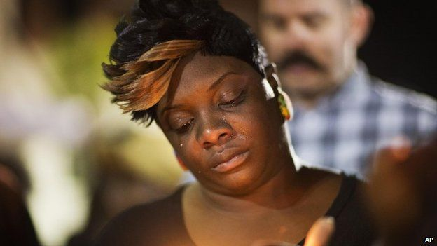 Tears roll down the face of Candice Ancrum, of Summerville, S.C., as she attends a candlelight vigil outside city hall protesting the shooting death of Walter Scott 8 April 2015