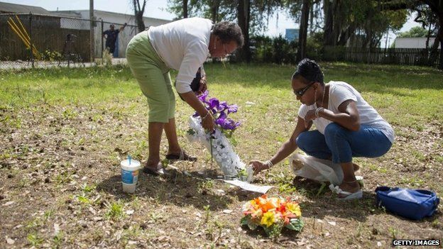 Barbara Scott (R), cousin of Walter Scott, the 50-year-old man who was killed after being fired at eight times as he ran away from an officer after a traffic stop, lays flowers with her mother Evaliana Smalls (L) at the lot where the incident happened in North Charleston, South Carolina on 8 April 2015