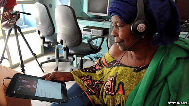A woman uses a tablet at an internet cafe in Dakar, Senegal