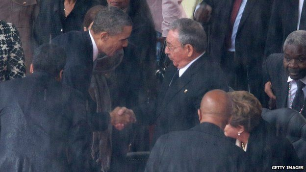 US President Barack Obama (L) shakes hands with Cuban President Raul Castro during the official memorial service for former South African President Nelson Mandela