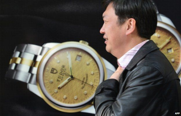 A pedestrian walks past a luxury watch shop in a major shopping district in Shanghai on 19 December 2013.