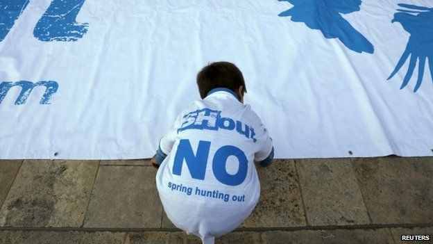 A boy arranges a banner on the ground during a rally organised by the Spring Hunting Out coalition in Valletta (08 April 2015)
