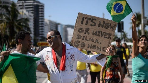 A man disguised as US singer Elvis Presley holds a placard during a protest against the government of Brazilian President Dilma Rousseff at Copacabana beach in Rio de Janeiro, Brazil on 12 April 2015