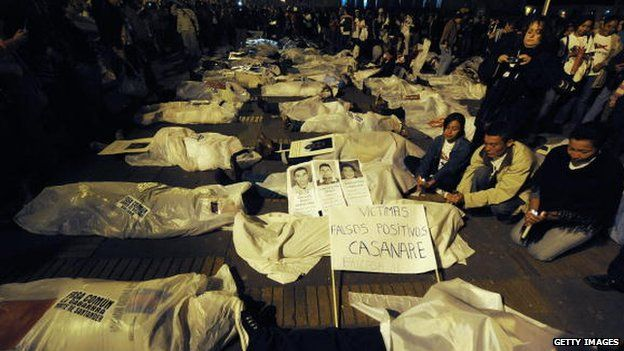 People demonstrate by covering themselves with sheets pretending they are false positive victims, during a protest against the false positives, massacres and forced disappearances by Colombian authorities on March 6, 2009, in Bogota.
