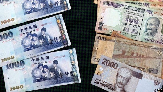 Taiwan dollar banknotes (L) lie lined up against banknotes of the Indian rupee and Indonesian rupiah on a table in Taipei, Taiwan, 13 April 2015