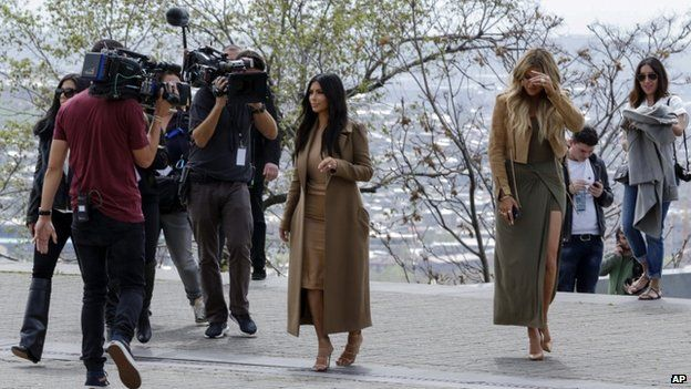 Kim Kardashian, centre, and Khloe Kardashian, right, walk in Victory Park while filming in Yerevan (9 April)