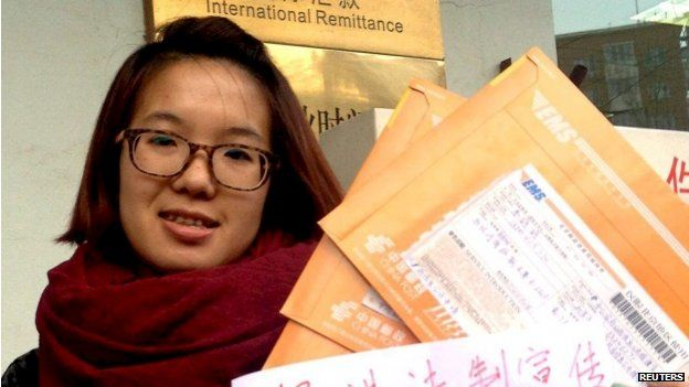 """Women activist Wei Tingting, 26, poses for a photograph with letters and a paper which read """"push ahead legal advocacy, request information disclosure, domestic violence should be punished by law!"""" in this undated file handout picture taken in an unknown location in China, provided by a women's rights group on 8 April 2015"""