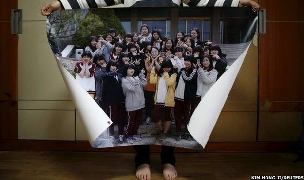 Eom Ji-yeong, mother of Park Ye-ji who died in the Sewol ferry disaster, poses for a photograph with a picture showing her daughter (44th from left in top row) with her schoolmates when she was 15