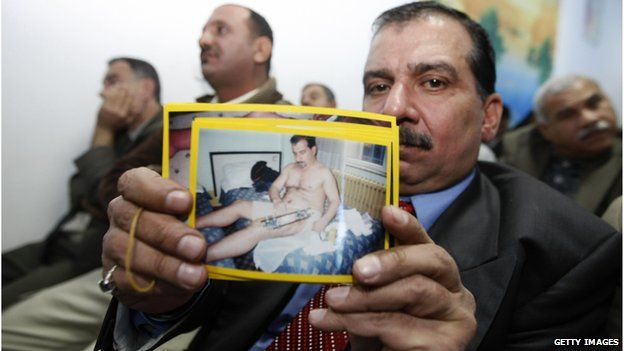 An Iraqi victim of a shooting incident holds up a picture of himself, during a meeting with US Federal Prosecutors to discuss the case against the security firm Blackwater