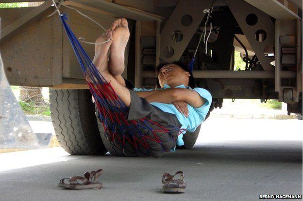 A man sleeps with his hammock underneath a truck