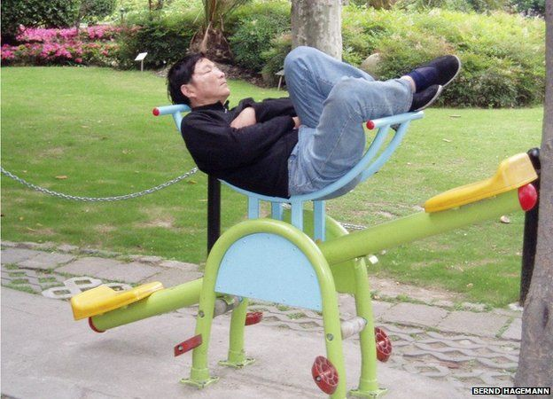 A man asleep on a child's see saw in China
