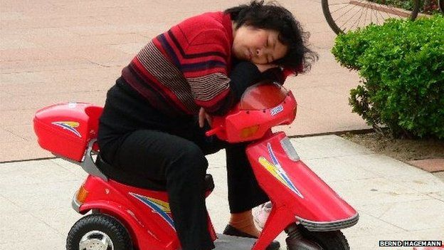 A woman sleeps on a child's scooter