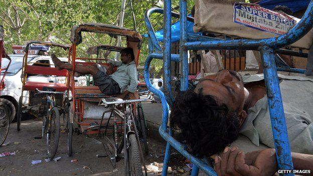 Indian rickshaw pullers sleep during the heat of the day in New Delhi on 10 June, 2014