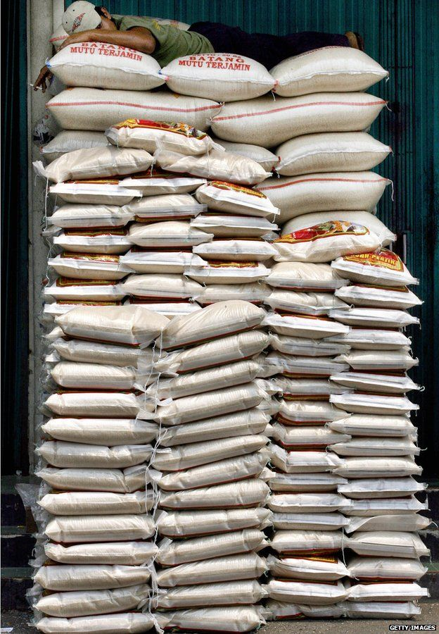 A labourer takes a nap on top of rice-sacks at a market in Jakarta, Indonesia, 5 September 2006