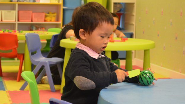 Chan Ka Chit, aged two, plays with a toy watermelon and toy knife during an HKYTA session