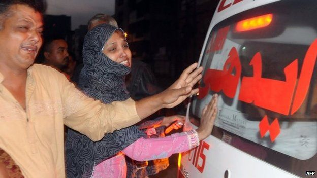 Relatives beside an ambulance mourn convicted murder Muhammad Faisal after his execution in Karachi on 17 March
