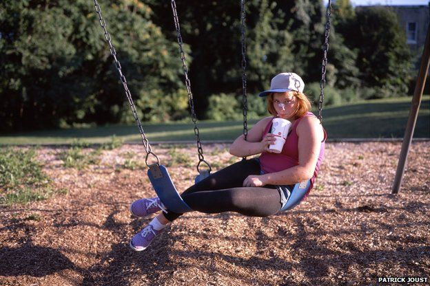 Photo of girl on swing drinking through straw