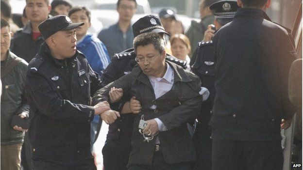 Police remove an unidentified man outside the Beijing court (17 April 2015)