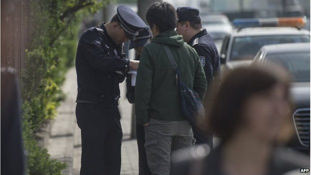 Police delete files in a Japanese journalist's camera outside the court in Beijing (17 April 2015)