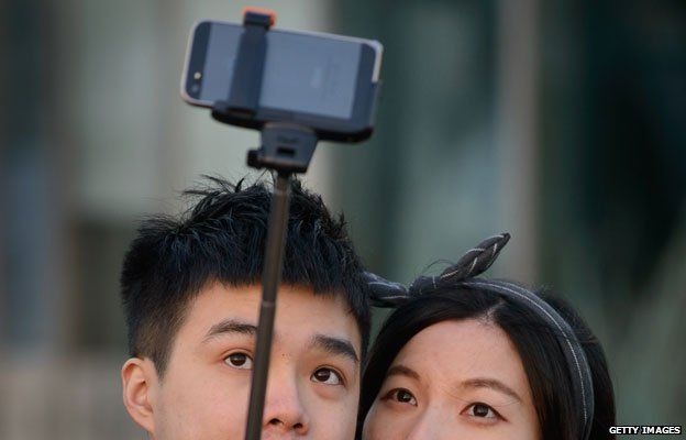couple take photo with selfie stick