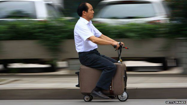 This picture taken on May 28, 2014 shows Chinese farmer He Liangcai riding a motorized scooter suitcase that he has spent the past ten years developing. It can travel up to 12.5mph