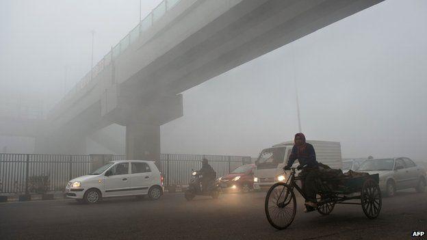 A rickshaw puller passes under a bridge early in Delhi