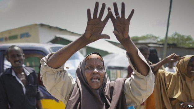 "Woman cheers as she looks at demonstrators chanting ""al-Shabab nichi"" (Down with al-Shabab) in Garissa"